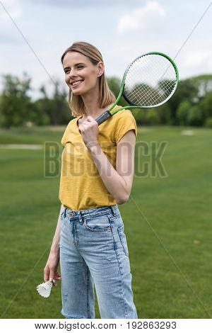 Attractive Blonde Girl Standing With Badminton Racquet And Shuttlecock While Looking Away