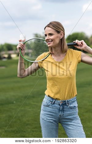 Attractive Smiling Woman Standing With Badminton Racquet And Shuttlecock In Park