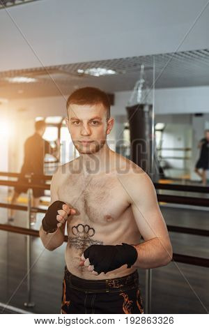 A Young Man Is Boxing In The Hall. Attentive Sportsman In The Boxing Hall Practicing Boxing Punches