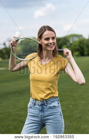 Happy Woman Posing With Badminton Racquet And Shuttlecock While Looking Away
