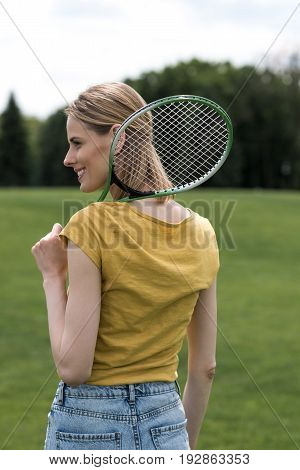 Back View Of Smiling Woman Holding Badminton Racquet And Looking Away