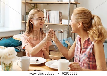 Mother-daughter care. Happy pretty mother and her beloved daughter feeding each other delicious cake while being in a perfect upbeat mood