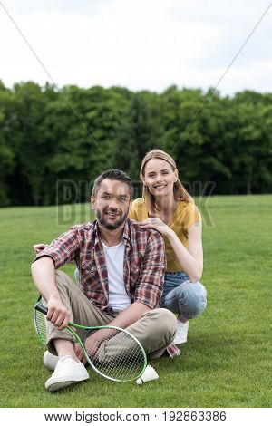 Happy Couple With Badminton Racquets And Shuttlecock Resting On Grass In Park