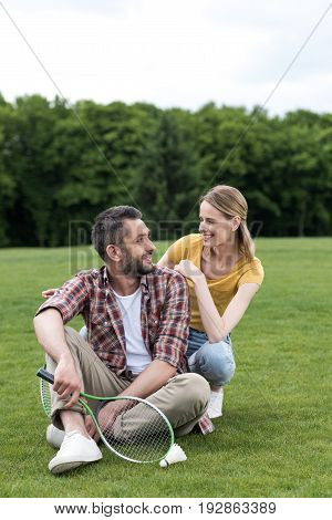 Happy Couple With Badminton Racquet And Shuttlecock Resting On Grass