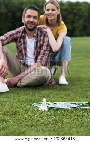 Shuttlecock And Badminton Rackets Lying On Grass, Happy Couple Sitting Behind