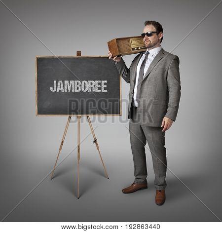 Jamboree text on blackboard with businessman holding radio