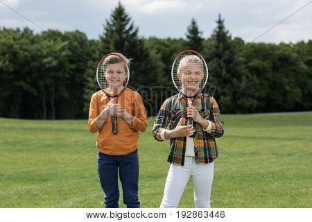 Adorable Little Children Holding Badminton Racquets And Smiling At Camera Outdoors