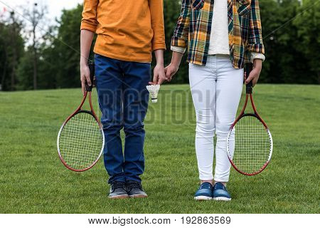 Cropped Shot Of Siblings With Badminton Racquets Holding Hands And Standing On Green Grass