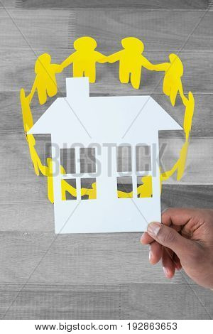 hand holding a house in paper against yellow paper cut out figures formimg circle on table