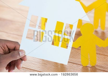hand holding a house in paper against yellow paper figures holding hands on wooden table