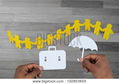 hands holding a schoolbag and an umbrella in paper against yellow paper cutout human chain on wooden table