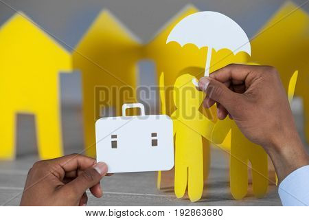 hands holding a schoolbag and an umbrella in paper against paper figures and houses on table