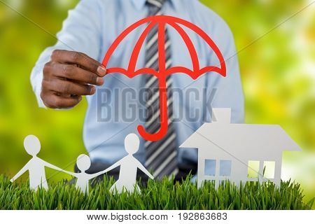 insurer protecting family by a red umbrella against detail shot of bright green leaves