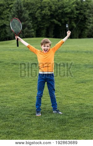 Cheerful Little Boy Holding Badminton Racquet And Triumphing While Standing On Grass