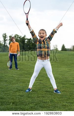 Happy child holding badminton racquet and triumphing while sibling standing behind
