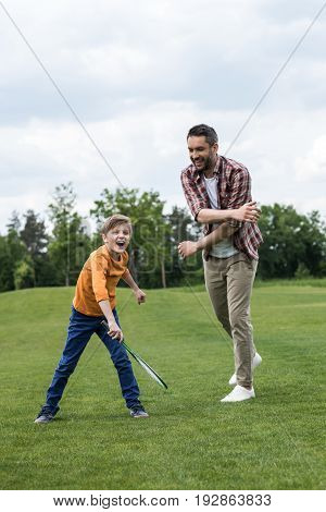 Smiling Father Teaching Happy Son Playing Badminton Outdoors