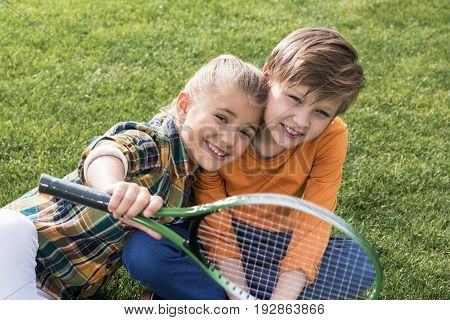 Happy Children Playing With Badminton Racquet While Sitting Together On Grass