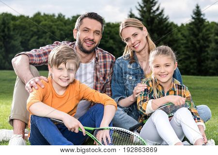 Happy family with two children holding badminton racquets and smiling at camera outdoors