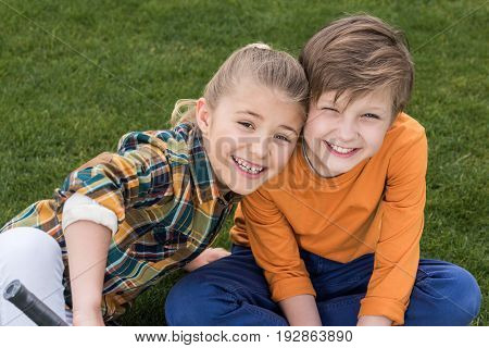 Adorable Happy Brother And Sister Sitting Together On Green Grass And Smiling At Camera