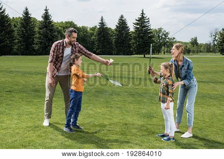 Parents teaching little kids how to play badminton outdoors