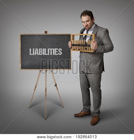 Liabilities text on blackboard with businessman and abacus