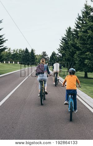 Back View Of Parents And Little Son Riding Bicycles In Park