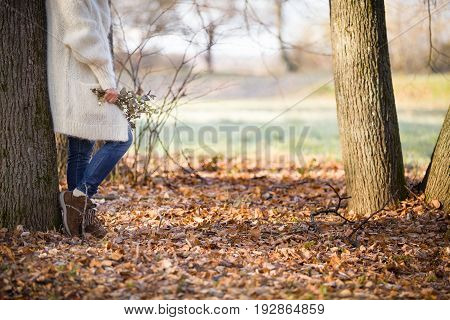 Woman standing near the tree and holding seasonal bouquet in her hands on a sunny autumn day in the park. Girl walking in the park and enjoying autumn. Lifestyle and autumn concept