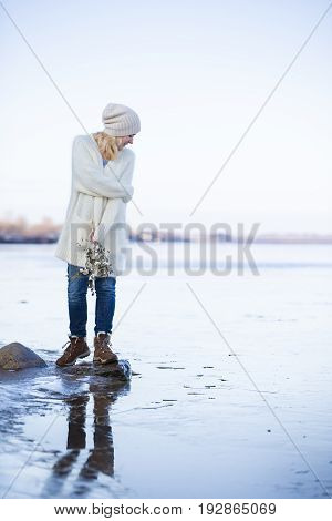 Closeup of beautiful young woman in warm clothes standing on a stone in water by the river shore. Girl enjoying winter sun and having fun outdoors. Lifestyle and winter concept.