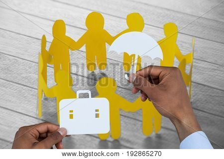 hands holding a schoolbag and an umbrella in paper against yellow paper figures forming circle on wooden table