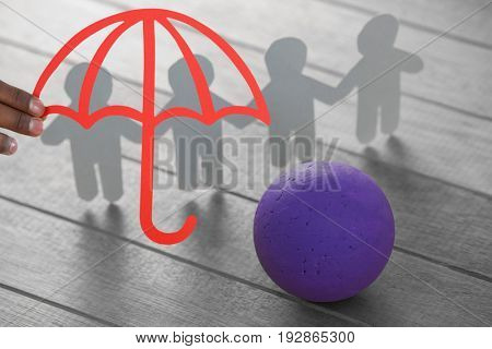 hand holding a red umbrella against paper cut out human chain by ball on wooden table