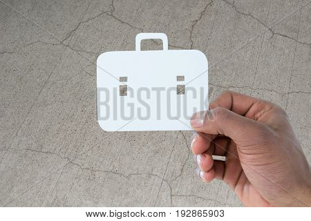 hand holding a schoolbag against gray cracked concrete wall