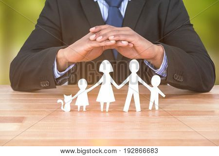 underwriter protecting family in paper with his hands against trees in grassy landscape