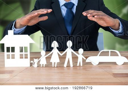 underwriter protecting family in paper with his hands against office buildings with graphs
