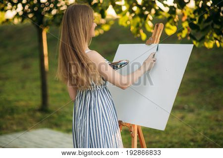 Beautiful Girl Draws A Picture In The Park Using A Palette With Paints And A Spatula. Easel And Canv