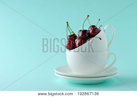 Sweet Cherry In Teacup On Cyan Background.