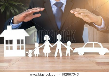 underwriter protecting family in paper with his hands against wood