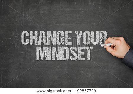 Cropped image of businessman writing change your mindset on blackboard