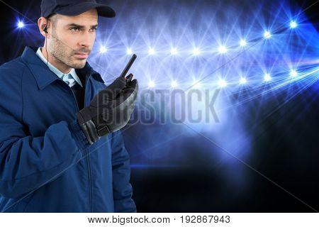 Focused security officer talking on walkie talkie against view of lights
