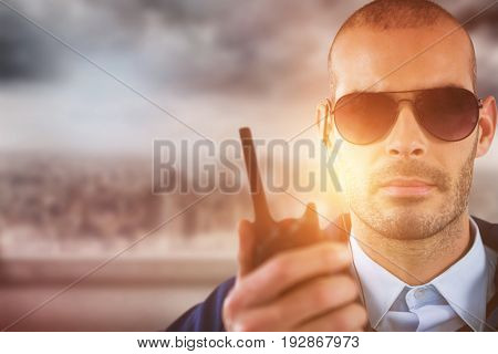 Portrait of security officer talking on walkie talkie against cityscape
