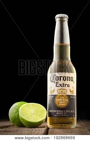 MINSK, BELARUS - APRIL 3, 2017: Editorial photo of bottle of Corona Extra Beer with lime on wooden table isolated on black with copy space. Corona is produced by Grupo Modelo with Anheuser Busch InBev