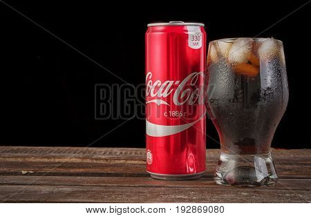 MINSK, BELARUS - JUNE 20, 2017: Coca-cola glass with ice and can on wooden table and copy space on black. Horizontal photo. Coca-Cola is a carbonated soft drink popular all over the world.