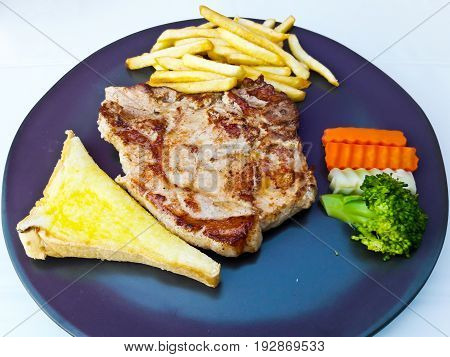 grilled pork chop (neck cut) with bread and french fries