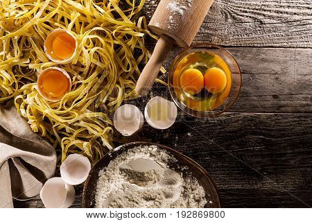 Process of cooking pasta with raw fresh ingredients for classic italian food - raw eggs flour on wooden table. Top View.
