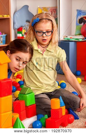 Children building blocks in kindergarten. Group kids playing toy on floor in interior preschool. Building a tower of cubes. Joint solution of assigned tasks.