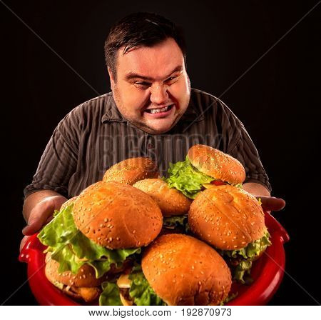 Fat man eating fast food hamberger and carries treat for friends on tray. Overweight person drops tray of food. Junk meal leads to obesity. Person regularly overeats concept on black background.