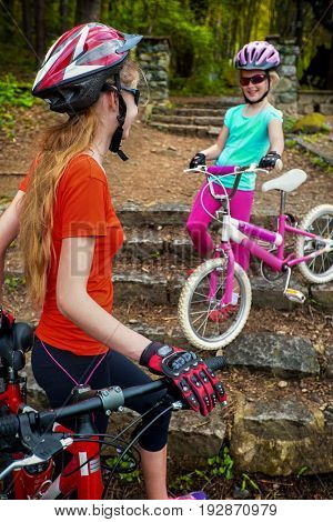 Bicyclist child ride on bicycle path in city. Children go down stairs in park. Mother with daughter have active leisure on fresh air outdoor. Tone image.