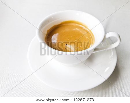 Hot coffee in a white cup on table