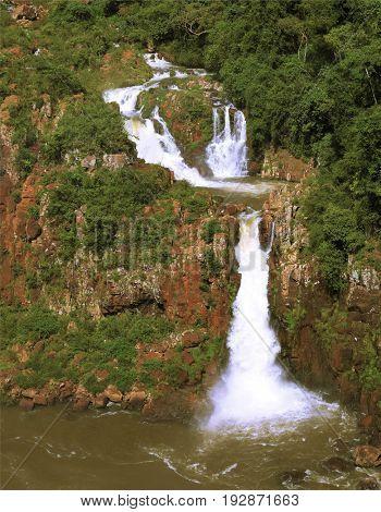 Multi-tiered cascades of water roar of lush jungle. The grand Iguazu Falls on the Brazilian side
