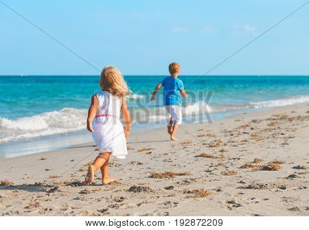 little boy and girl running on beach, family vacation
