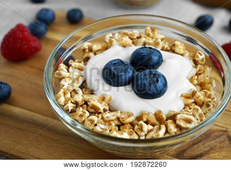 Healthy diet breakfast with a bowl of yogurt spelt flakes and fresh blueberries fruit.